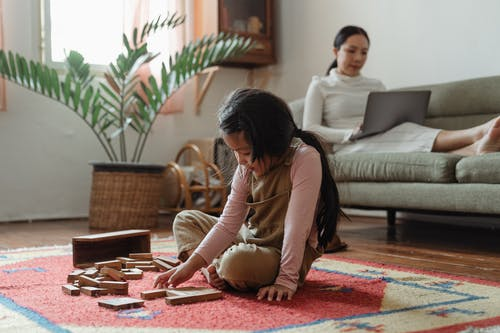 Content little Asian girl in casual wear sitting on carpet on floor and playing tower game while focused mother working on netbook on sofa near houseplant