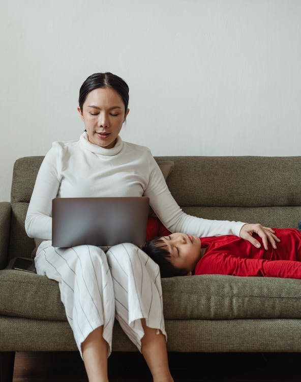 Positive Asian woman working on laptop on sofa in living room and hugging calm adorable son in casual clothes