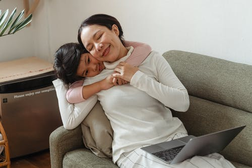 Happy mother and daughter hugging on sofa