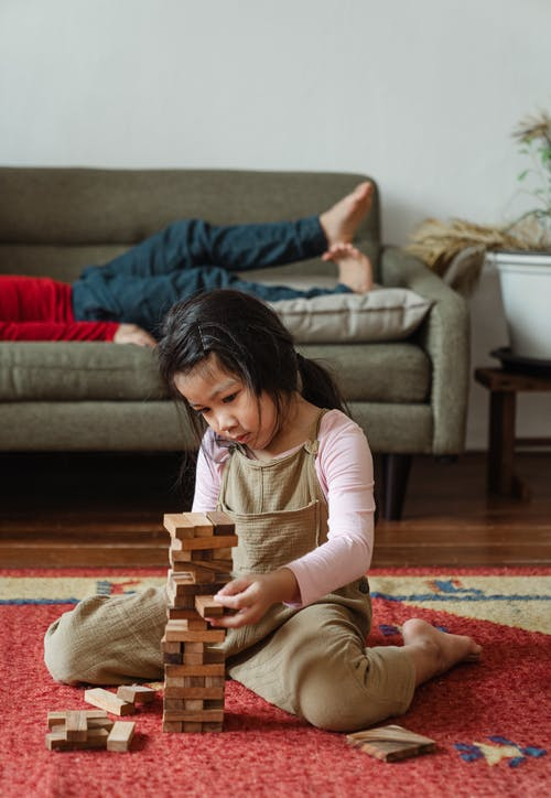 Little girl playing tower game on floor
