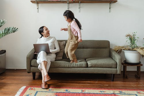 Happy mother with laptop talking to little daughter on couch