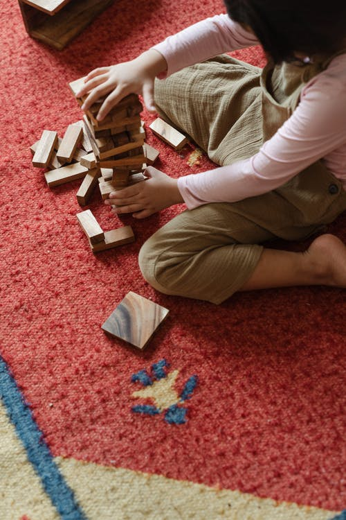 From above crop anonymous child sitting barefoot on carpet on floor and playing tower game alone in daylight