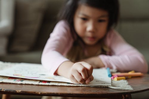 Crop concentrated Asian girl sitting at table and drawing on paper with colorful crayons in daytime