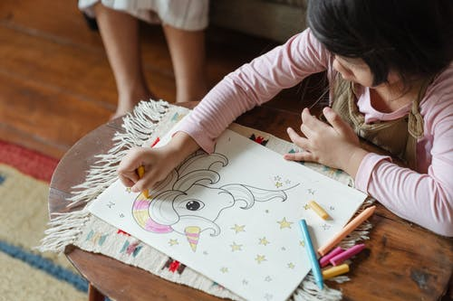 Crop cute girl drawing in coloring book