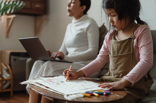 Focused girl drawing on paper near mother with laptop