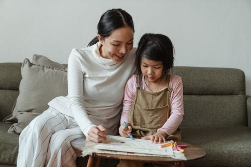Cheerful mother and daughter drawing on paper