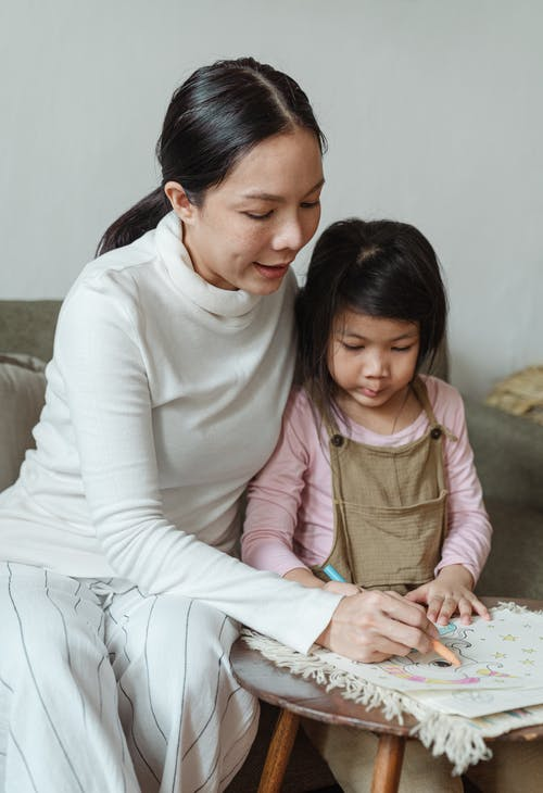 Mother and daughter coloring drawings on paper