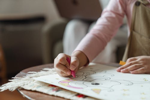 Crop unrecognizable child in light pink turtleneck sitting at coffee table and coloring pictures of coloring book by using multicolored crayons