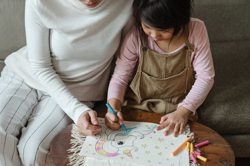Crop little girl with mother coloring picture of unicorn