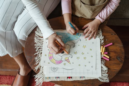 Crop mother and daughter coloring drawing on coffee table
