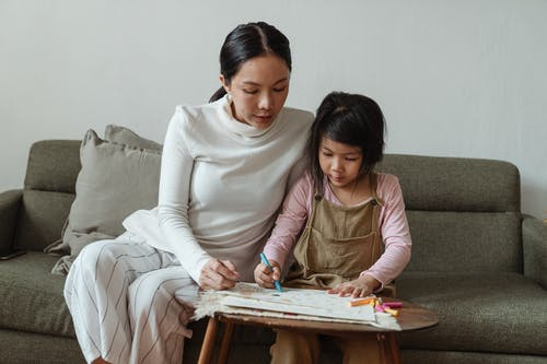 Caring ethnic mother watching daughter drawing picture