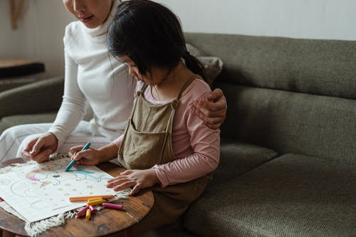 Focused ethnic girl coloring drawing together with mother