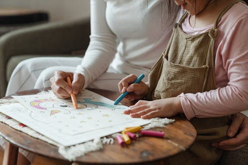Crop mother and daughter coloring drawing together on coffee table