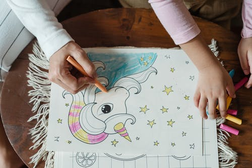 From above of crop anonymous mother and daughter coloring picture with unicorn with wax crayons on coffee table