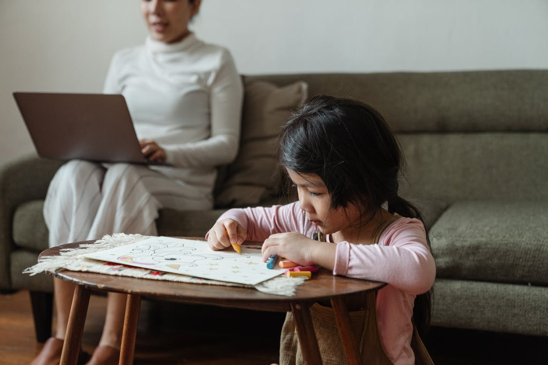 Little Asian girl coloring drawing in front of mother using laptop