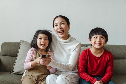 Cheerful ethnic mother and children choosing TV channel using remote