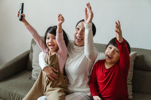 Positive ethnic mother with children watching football on TV and celebrating goal