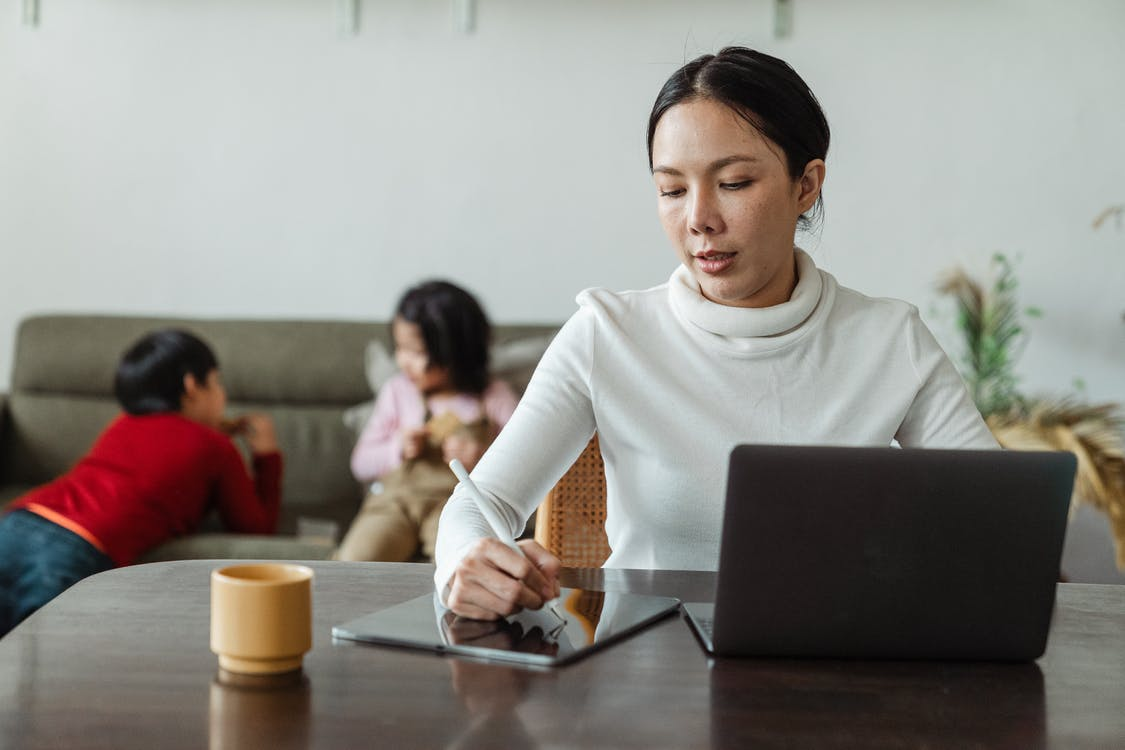 Focused young Asian woman in casual wear writing with stylus on tablet and browsing laptop while working remotely at home with children
