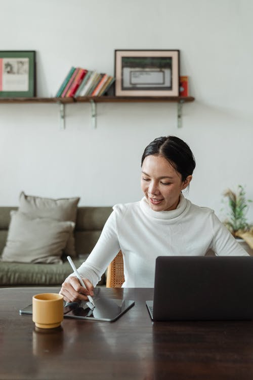 Young Asian female freelancer using gadgets while working at home