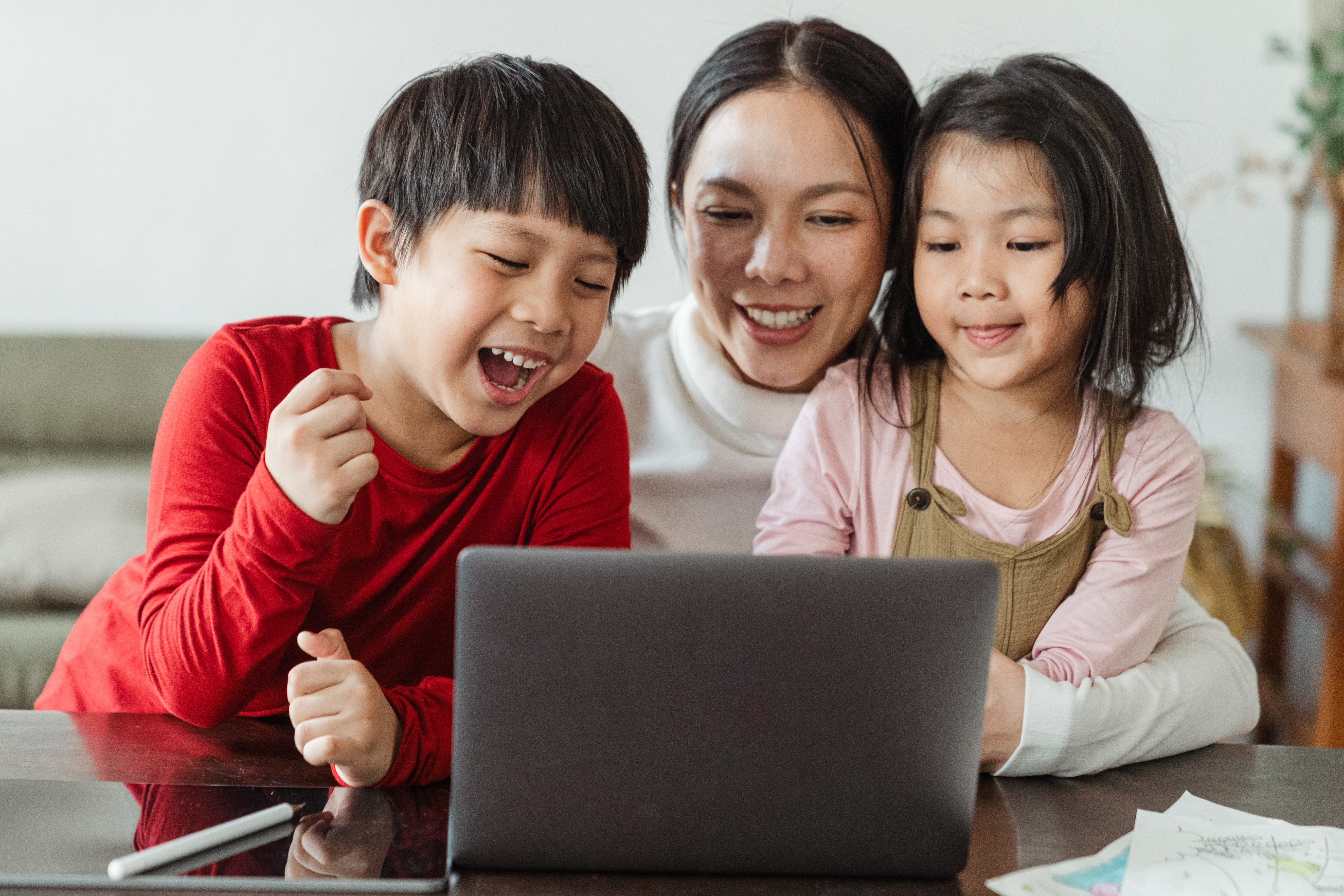 happy ethnic mom and kids watching cartoon on netbook at home