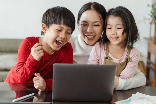 Cheerful little Asian boy and girl watching funny video on laptop with happy smiling mother during weekend