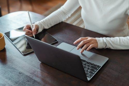 Crop faceless female entrepreneur doing multitasking work on different devices