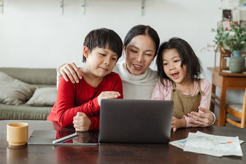 Adorable little ethnic children watching funny video on laptop with mother