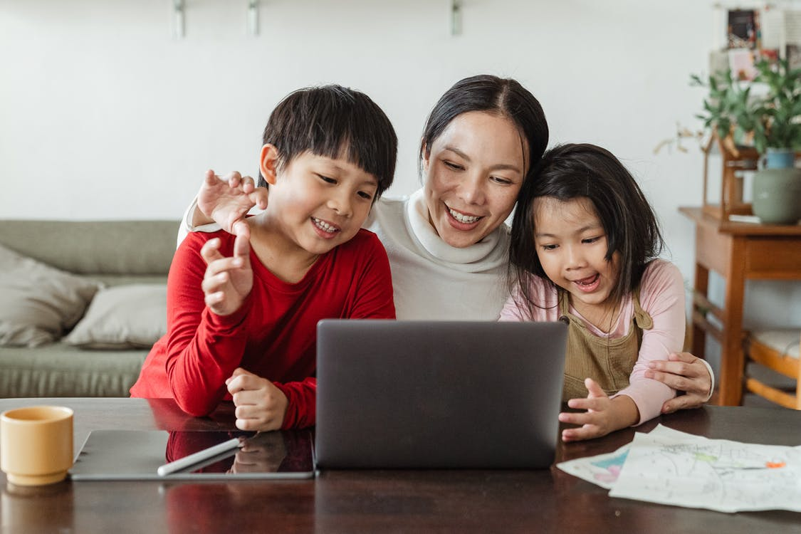Positive mother and little children watching cartoon on netbook at home