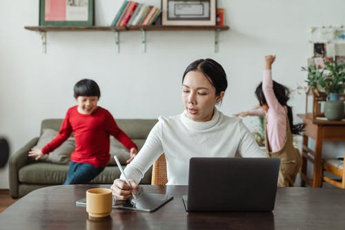 Asian mother working online using laptop and taking notes on tablet with stylus and cheerful children making noise and running behind in living room