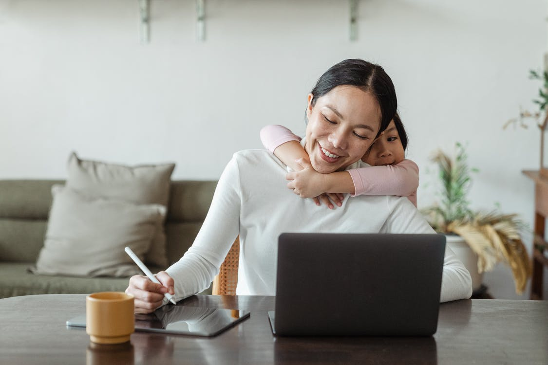 Happy mother working from home and little daughter hugging mom