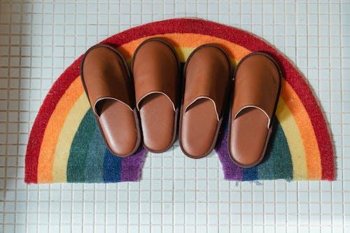 Brown leather slippers on rainbow bathroom mat