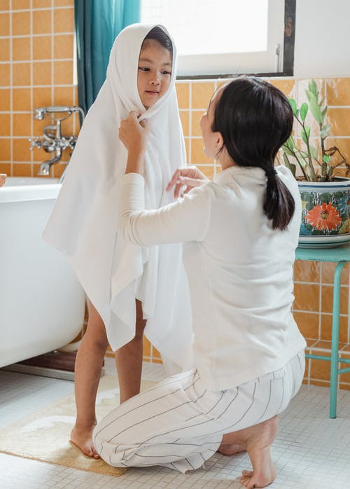 Mother wiping daughter with towel in cozy bathroom