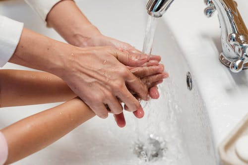 Crop mother washing hands of kid in washbasin
