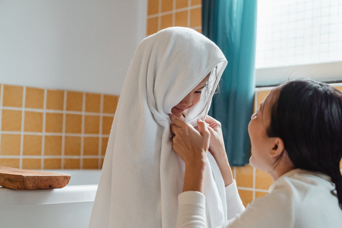 Cheerful ethnic mum wiping cute little daughter with big fluffy towel in modern bathroom at home