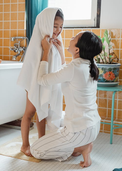 Cheerful ethnic mother wiping happy little daughter with large white towel in cozy light bathroom