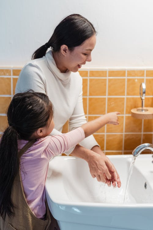 Ethnic mother and daughter washing hands together in bathroom