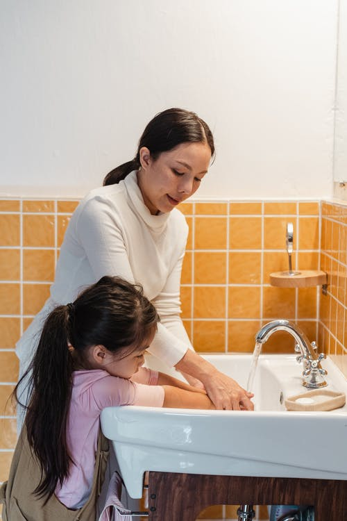 Side view of ethnic mother teaching adorable little daughter to wash hands in big white washing basin in modern bathroom