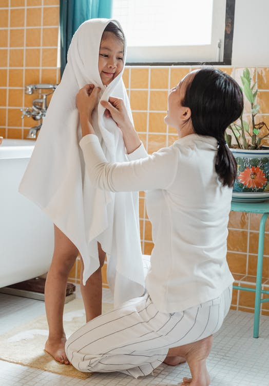 Asian mom tenderly wiping little daughter with bath towel