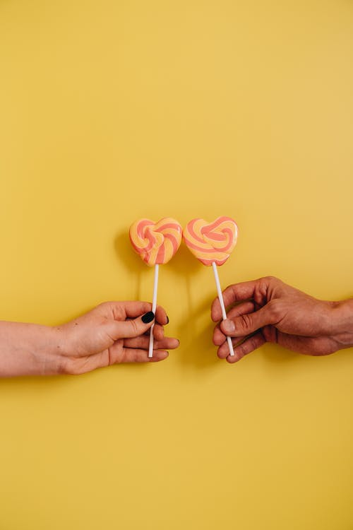 Couple Holding Heart Shaped Lollipops on Yellow Background
