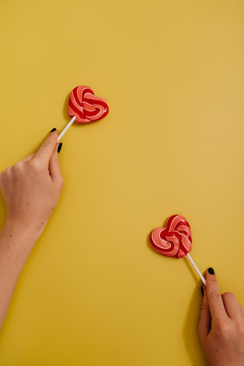 A Person Holding Two Heart Shaped Lollipops Far From Each Other on Yellow Background