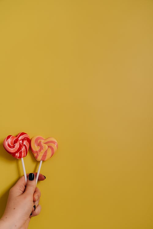 Gratis lagerfoto af delikat, gul baggrund, hånd, hjerte