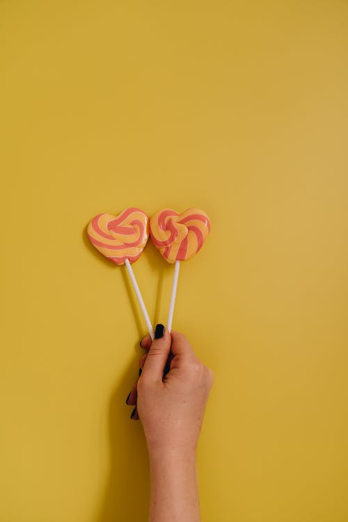 A Person Holding Two Heart Shaped Lollipops Next to Each Other on Yellow Background