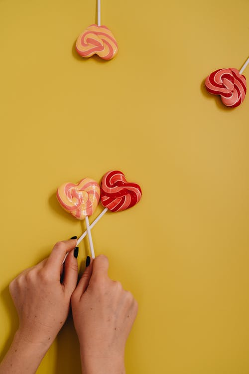 A Person Holding Two Heart Shaped Lollipops on Yellow Background