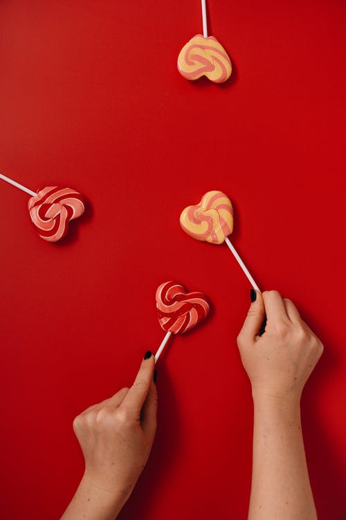 Person Holding Heart Shaped Lollipops