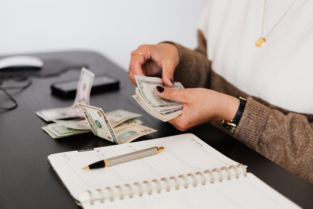 A person counting money. | Photo: Pexels