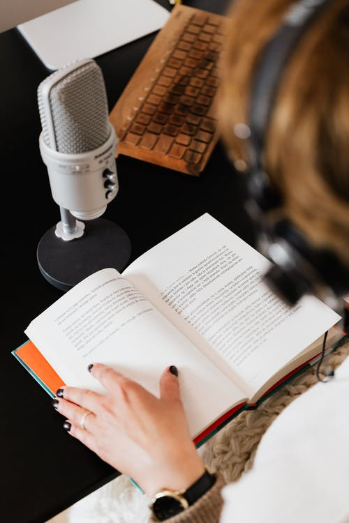 High angle of elegant female audiobook narrator recording audiobook while sitting at desk with microphone