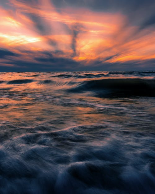 Majestic view of stormy sea with foamy waves under vivid sundown sky in long exposure