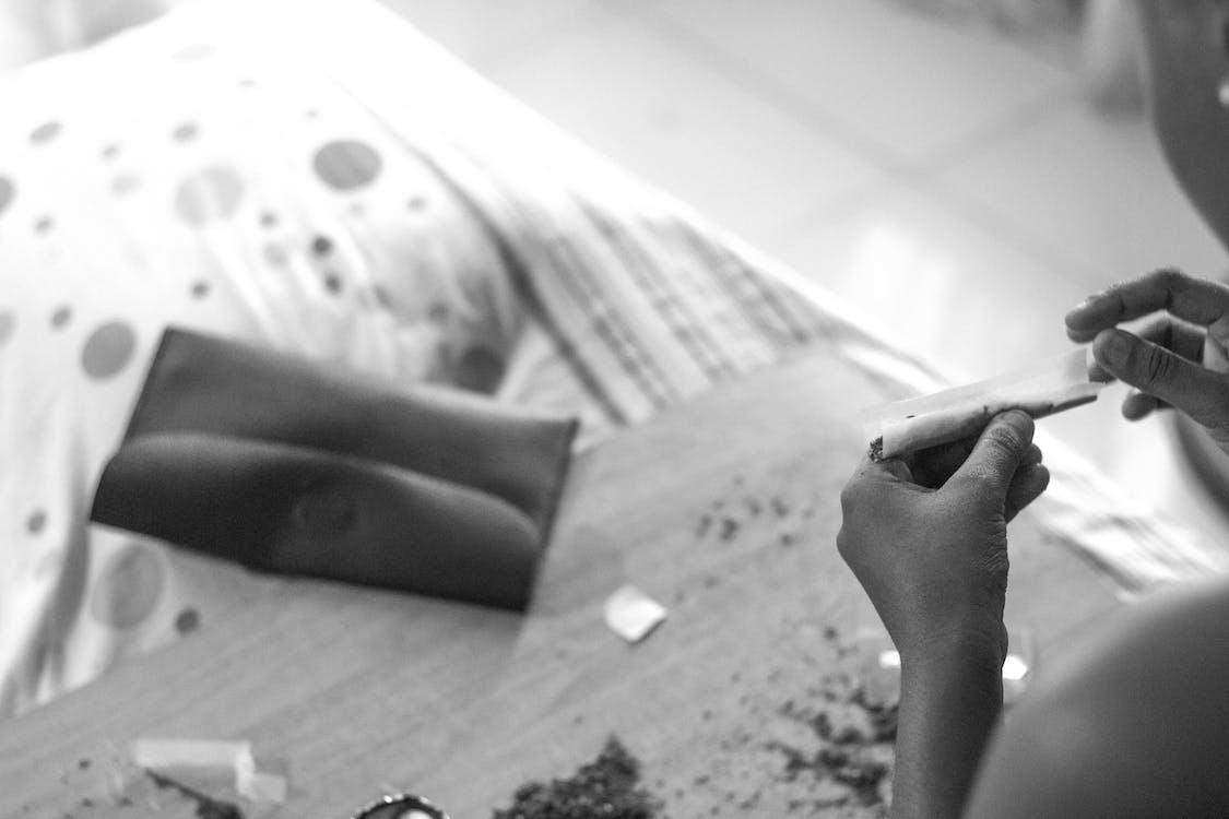 Unrecognizable person making cigarette at home