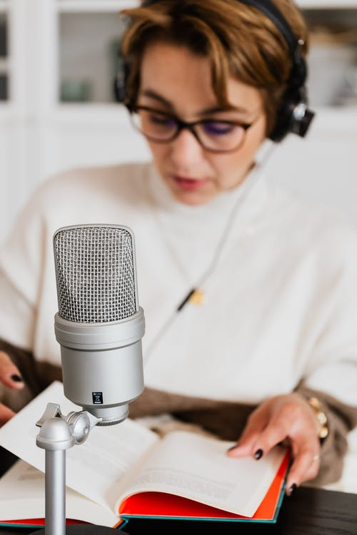 Photo of Condenser Microphone Near Woman Reading a Book