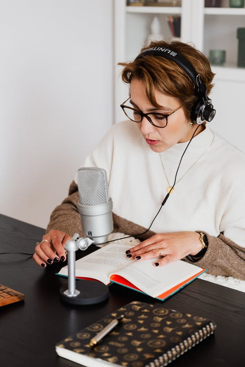 Woman Reading a Book While Wearing Headphones